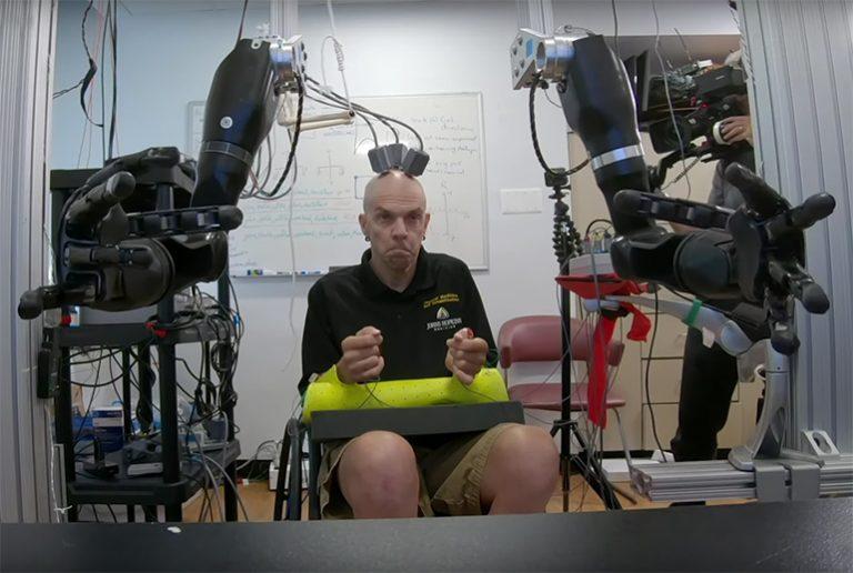 L'homme contrôle simultanément deux bras robotisés par la pensée